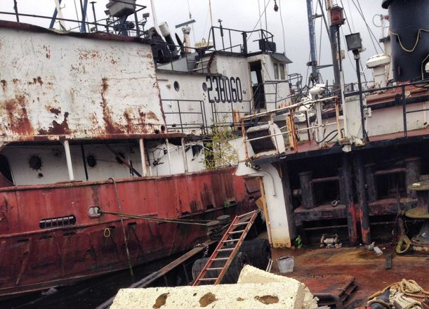 Side view of a rusty, abandoned ship.