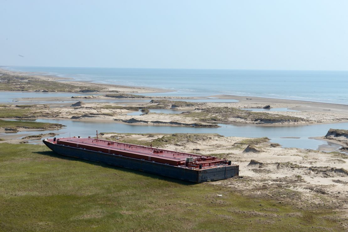 Grounded barge next to body of water.