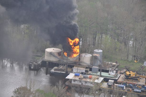 Fire burning on an oil platform on the water.