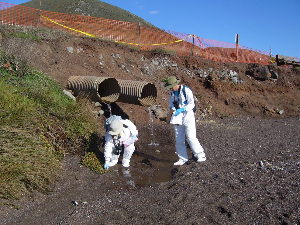 Two people working on a beach near a drainage pipe.