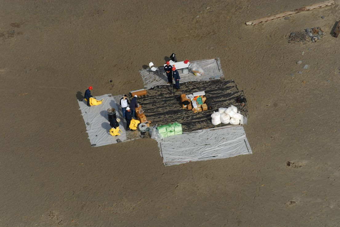 Aerial view of workers on a beach with tarps.