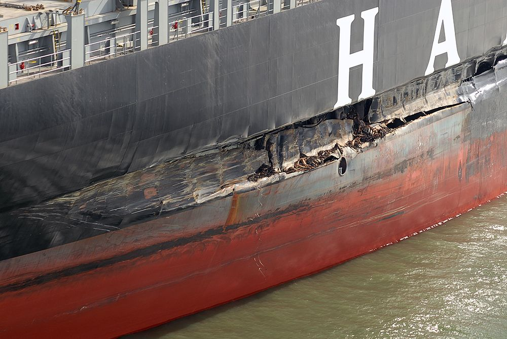Photo of ship's hull with large gash.