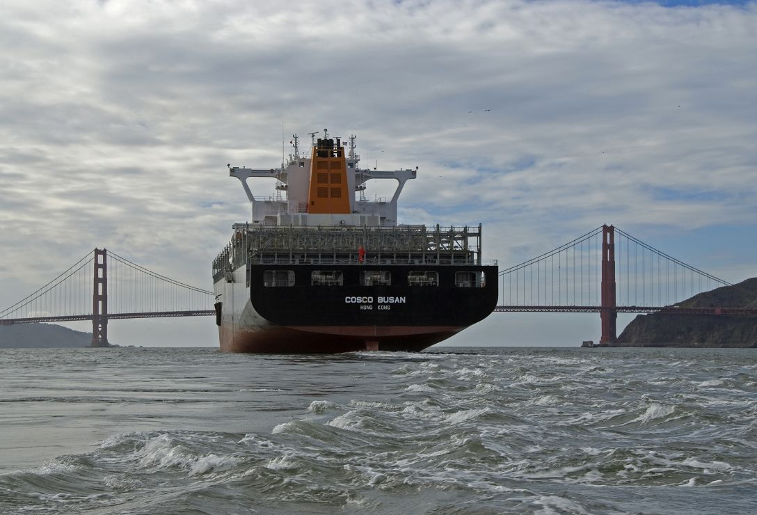 Large vessel moving away from the viewer, towards a bridge.