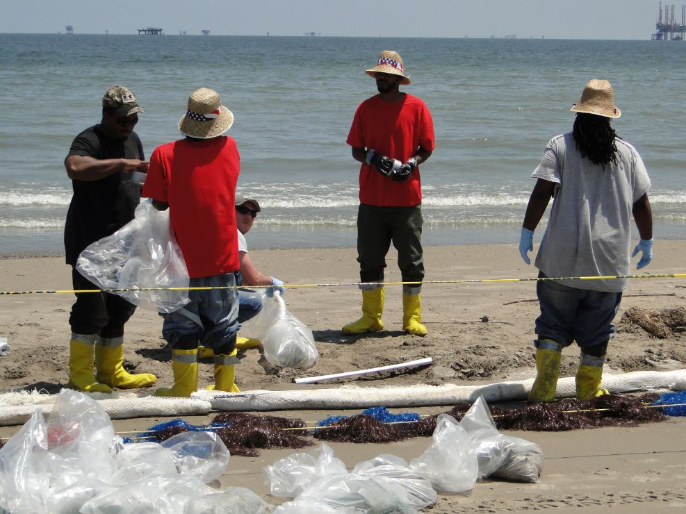 Workers using pom-poms to absorb oil washed onto the beach.