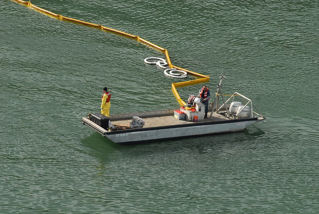 Workers standing in a boat placing boom on the water.