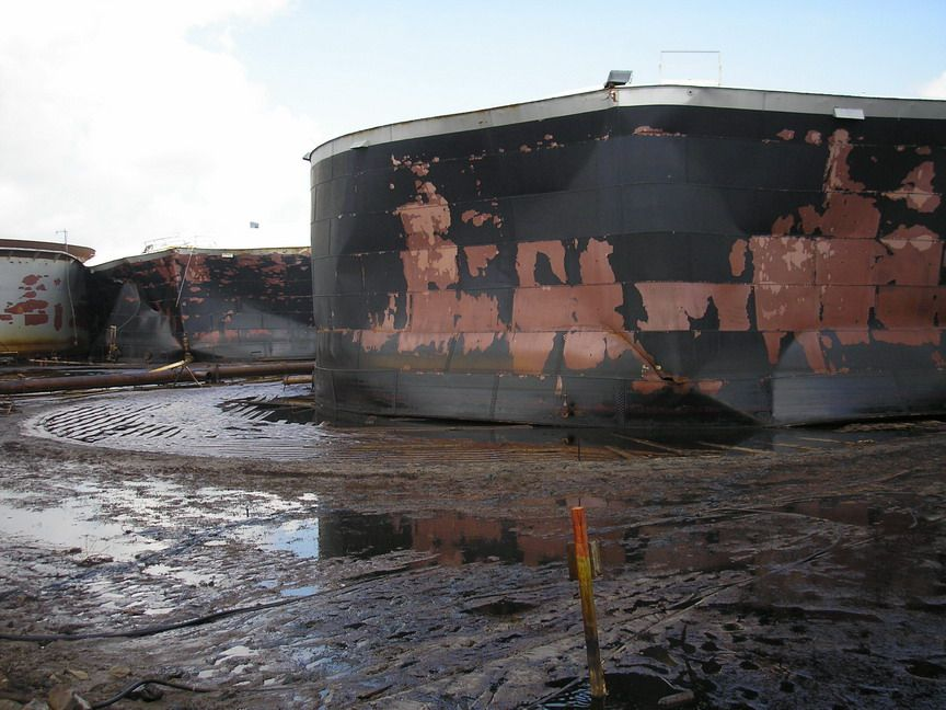 Large oil tank with oil pooled around it.