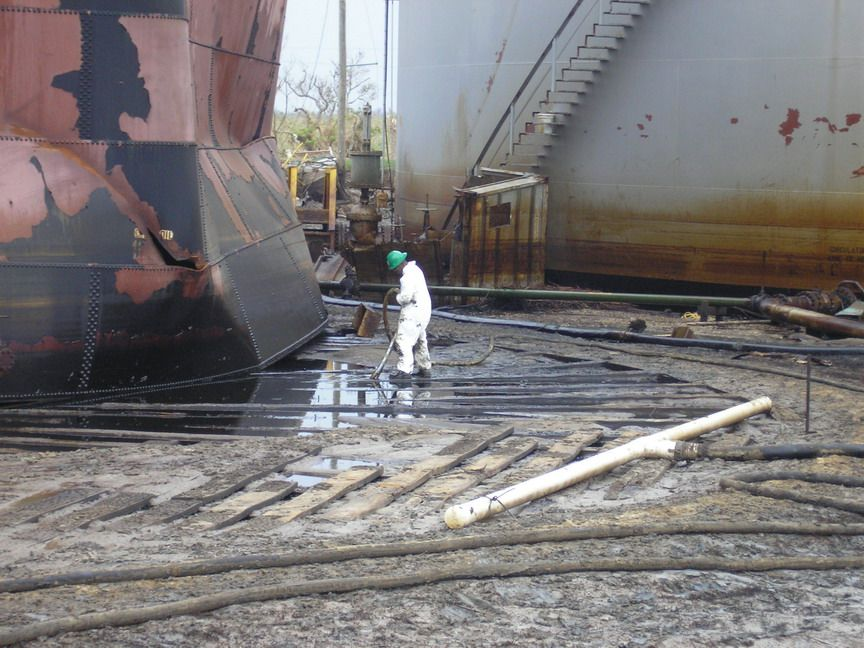 Worker vacuuming oil next to large tank.