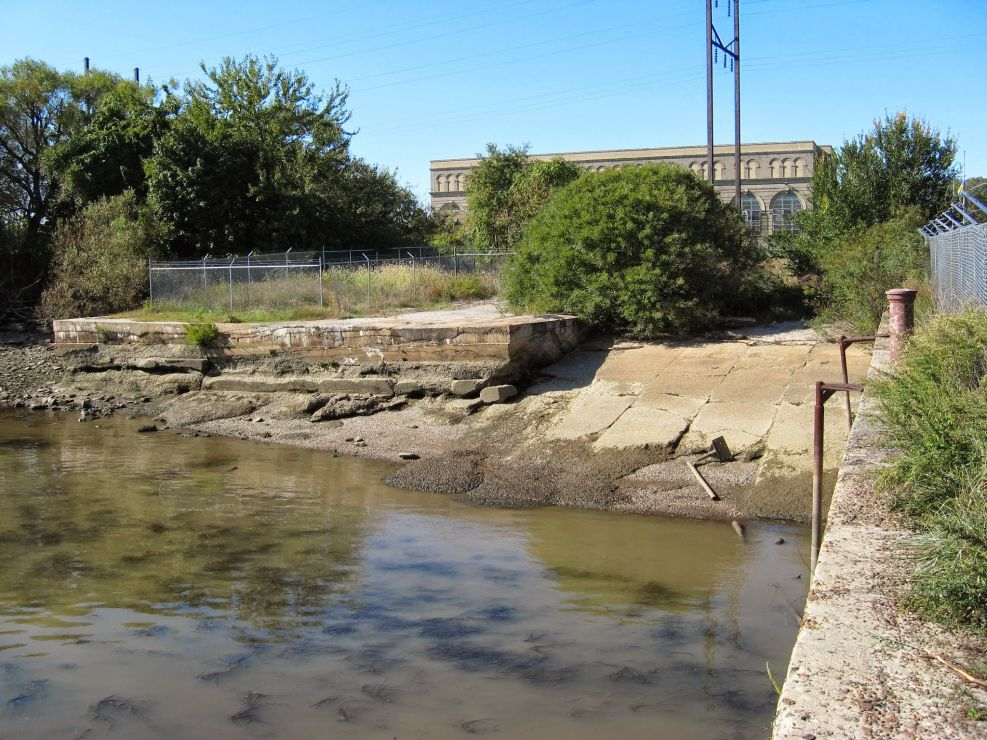 Un-restored riverbank with weeds and cement.