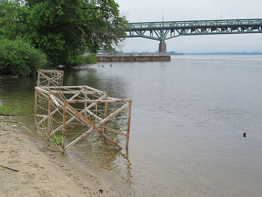 Wooden frame structure partially submerged in the water by the river's edge.