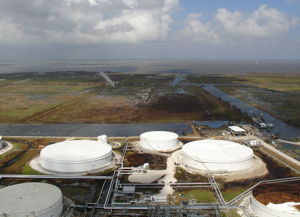Large oil tanks with oiled marsh in background