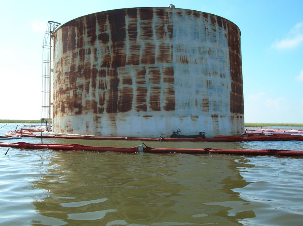 Large oil tank surrounded by boom in water.