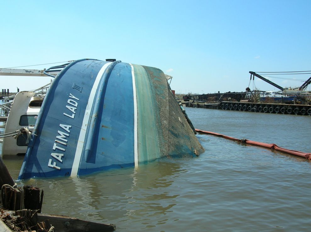 Overturned fishing vessel in water.