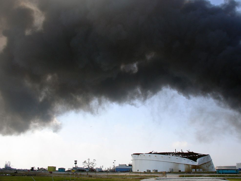 An oil tank with black smoke bowing over and above it.