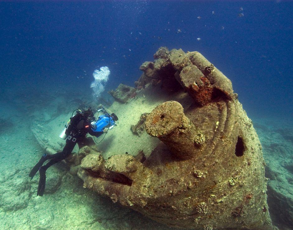 Diver exploring sunken wreck.