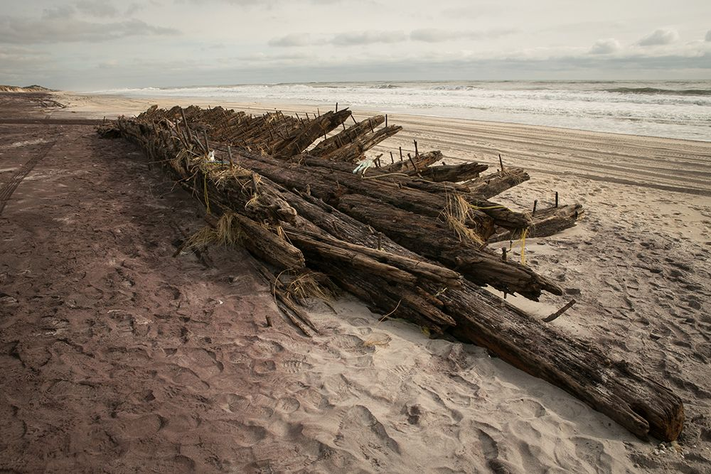 Ship's wooden skeleton on a beach.