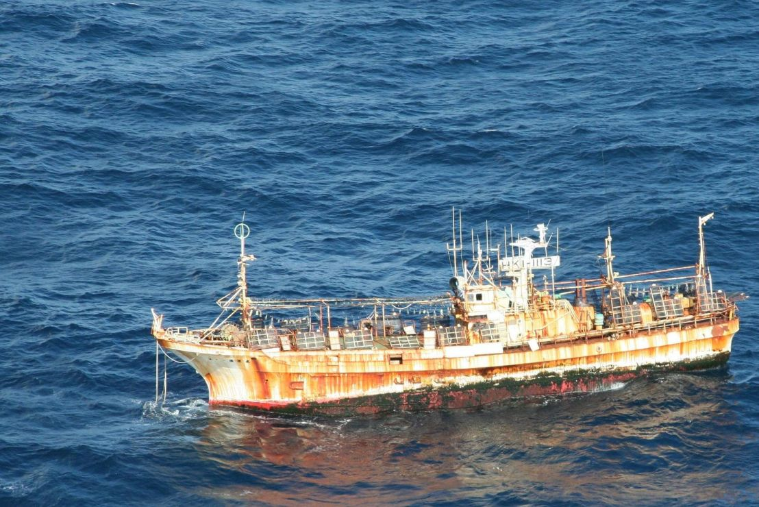 Rusted fishing vessel in the ocean.