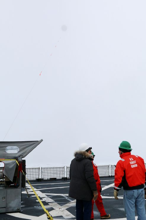 People on deck watch a balloon sensor tethered to the ship flying high above.