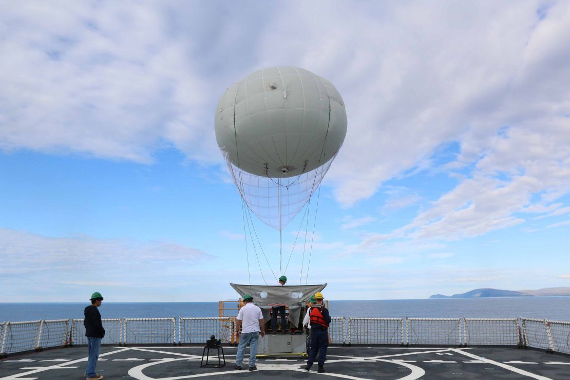 People release giant balloon tool into air from ship deck.