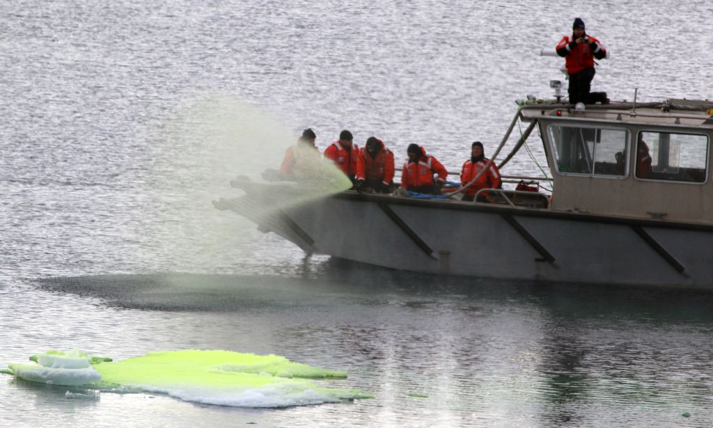 People in a boat spraying green dye into Arctic Ocean.