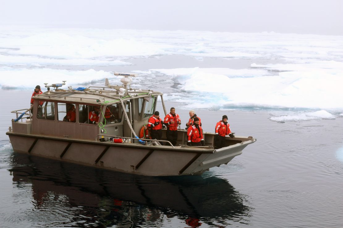 People on the Arctic Survey Boat amid icy waters.