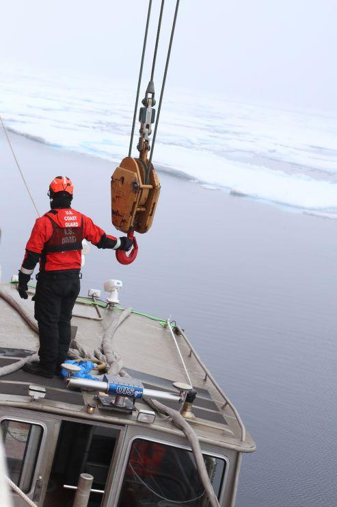 U.S. Coast Guard member prepares a crane to launch small survey boat.