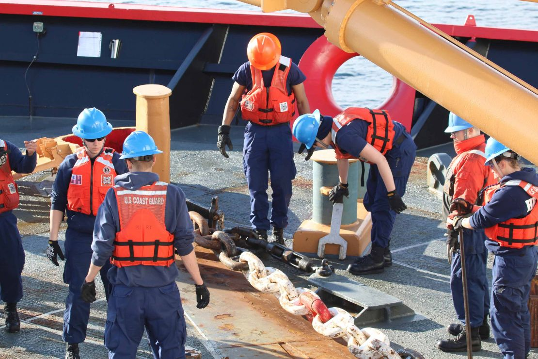Crew members prepare a giant ship anchor onboard.