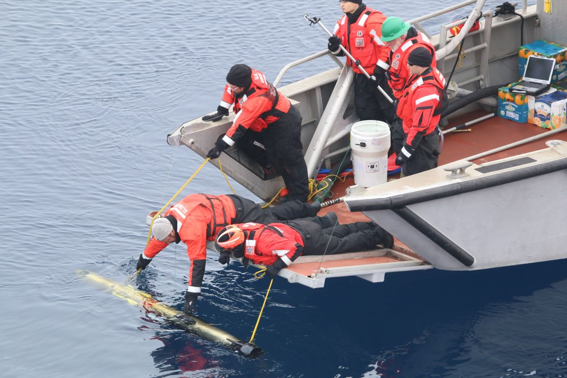 People lean off a small boat to deploy an automated underwater vehicle in water