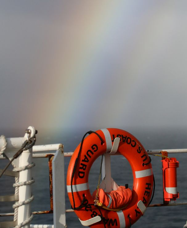 Rainbow over the edge of a ship with a life preserver.