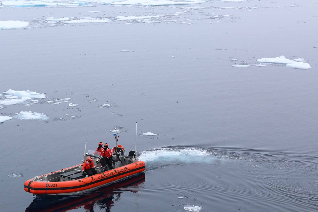 Coast Guard members in small boat on Arctic Ocean.