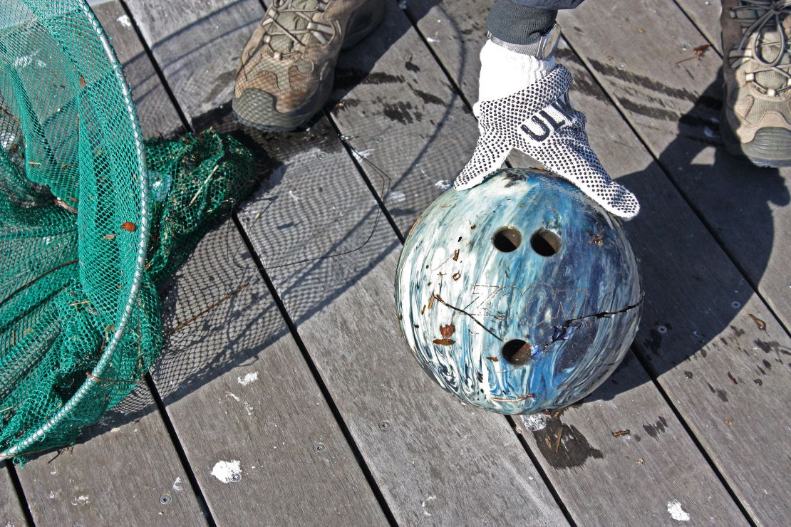 A cracked bowling ball with a net used to scoop it out of a river.