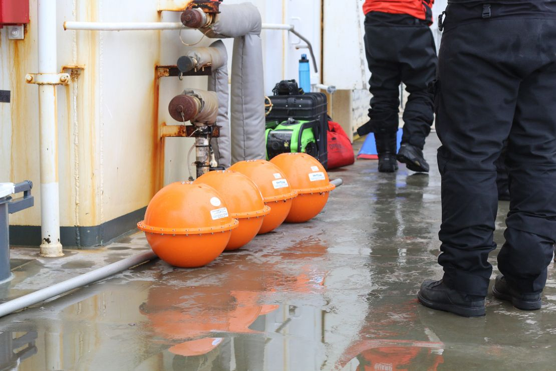 Four orange iSphere buoys lined up on the deck of the ship.