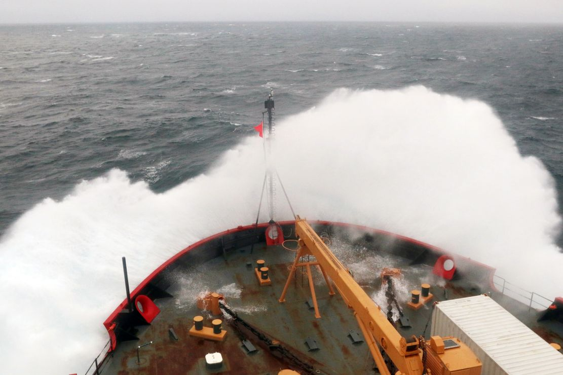 Large wave breaking on the bow of a ship.