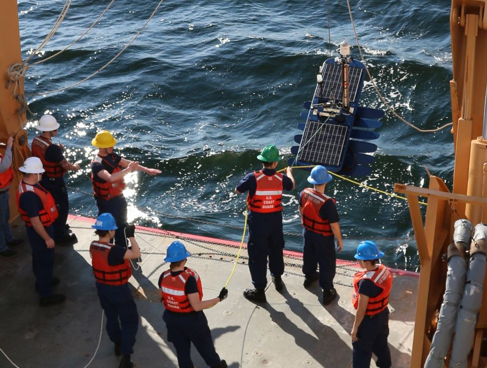 Ship crew lowers a oceanographic instrument into the ocean.