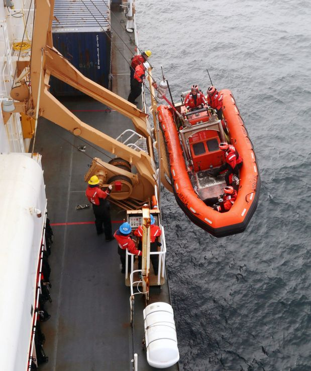 Ship crew hoists small boat from ocean back onto the vessel.