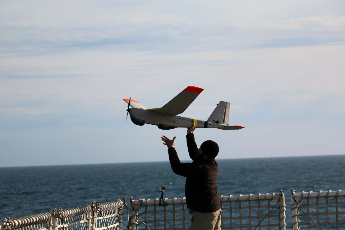 Person launches a remote-controlled plane by hand from a ship deck.