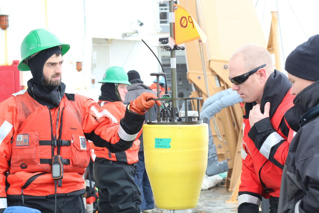 Scientists prepare to launch a small buoy from a ship.