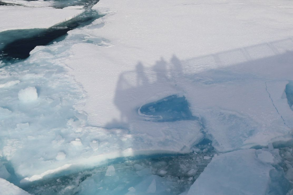 Shadows of people standing on a ship deck darken sea ice.