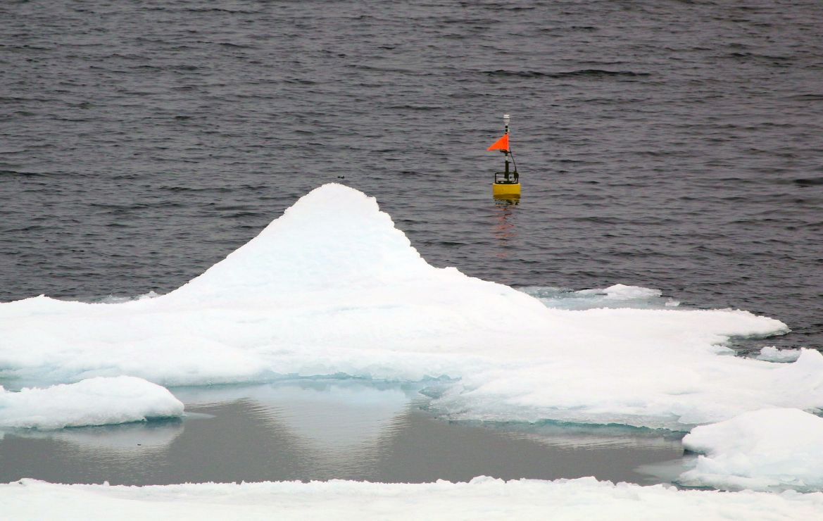 Oceanographic buoy floating at sea among ice.