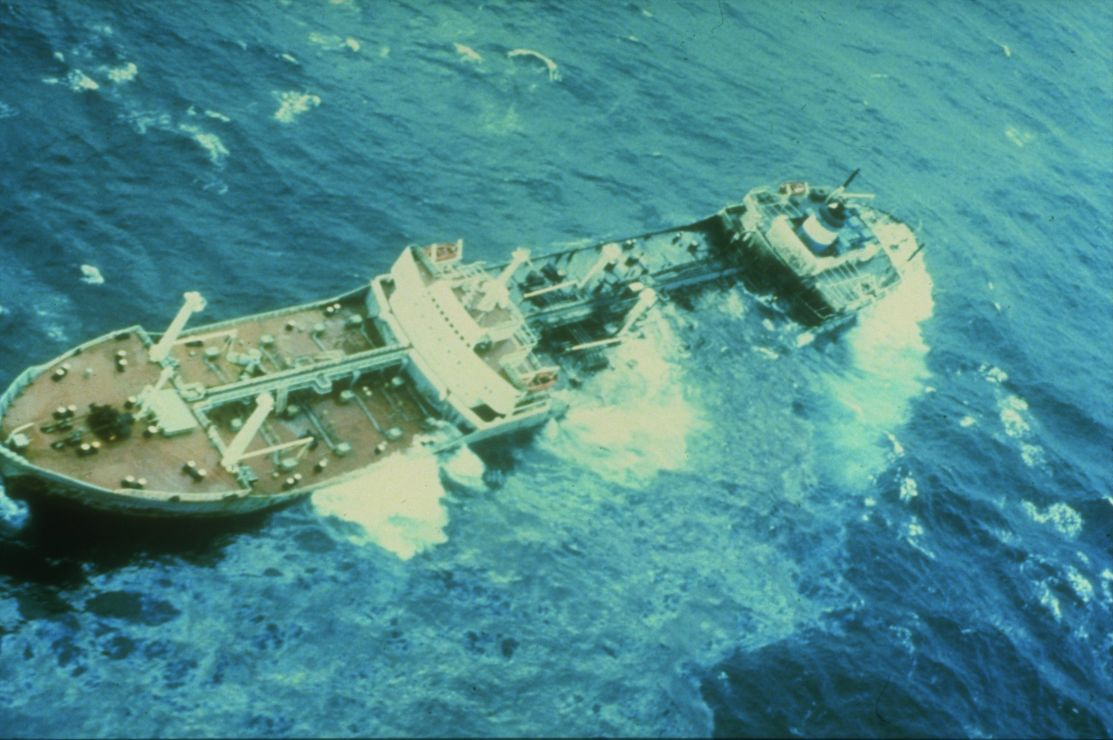 Oil is visible surrounding a sinking vessel, as waves wash over the side.