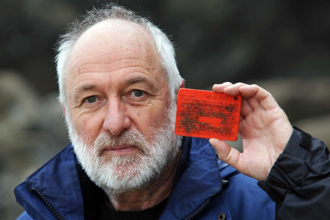 Man holding a small orange plastic drift card.