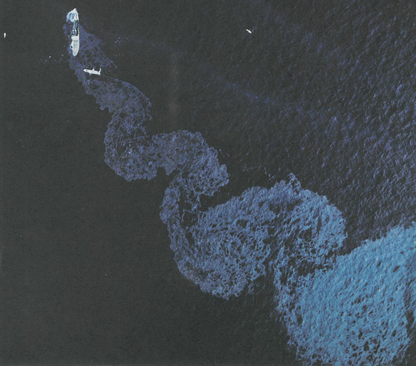 A wave-like oil slick emanates from a large sinking ship.