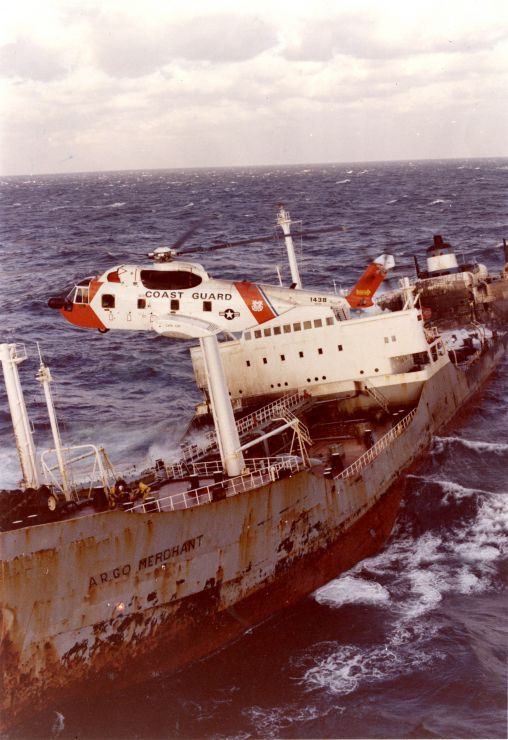 A Coast Guard helicopter hovers over a foundering rusted ship.