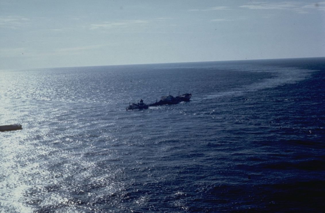 View of a trail of oil emanating from a foundering vessel at sea.