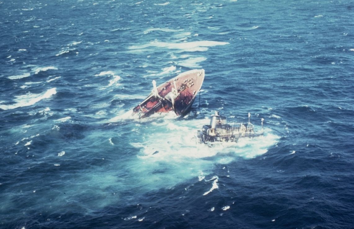 A sinking vessel's bow and stern have separated in high seas.