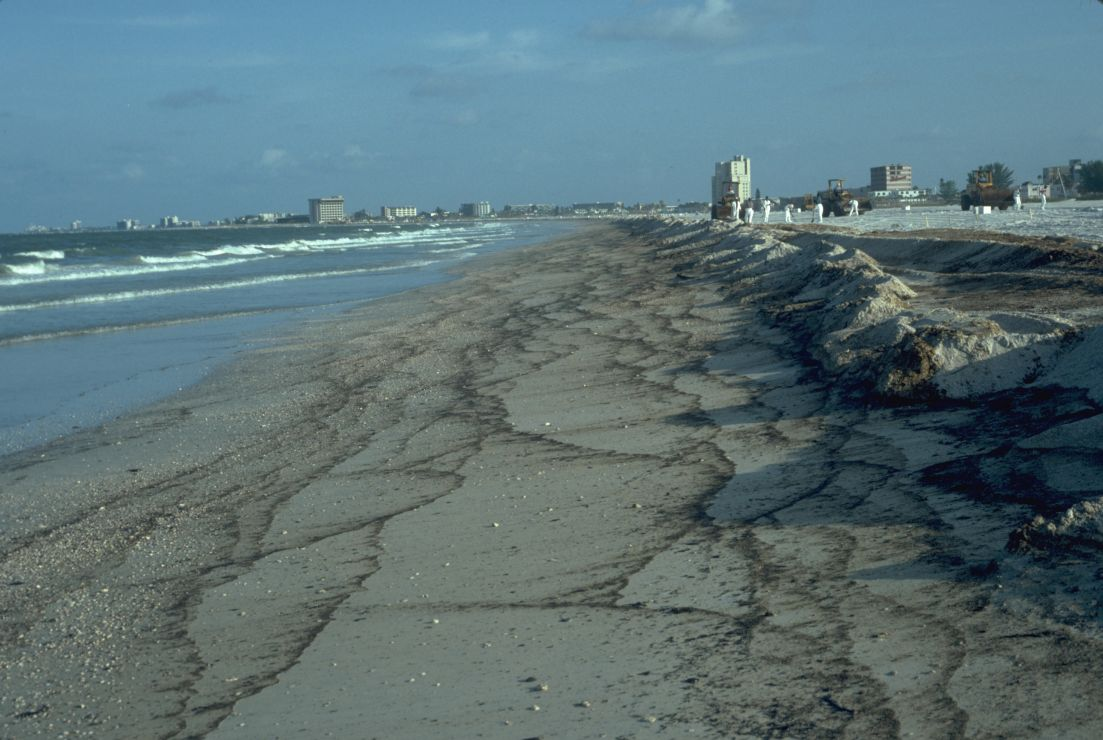 Photo: Multiple interlaced streaks of brown oil on a long section of beach.