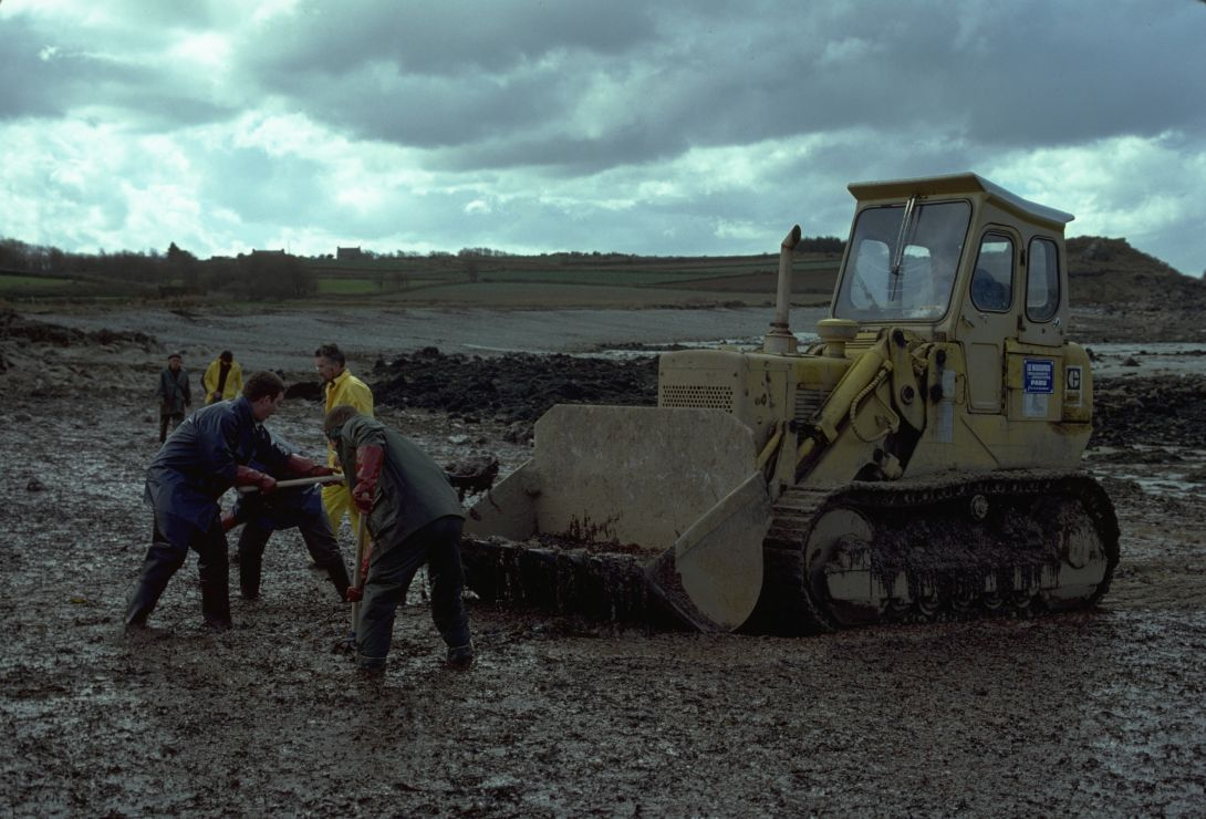 Photo of workers and an excavator working on an oiled gravel beach.