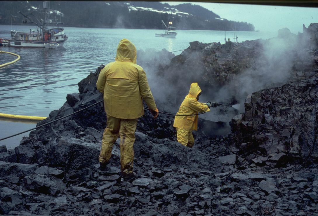 Photo of two workers spraying heavily oiled rocks with hot water.