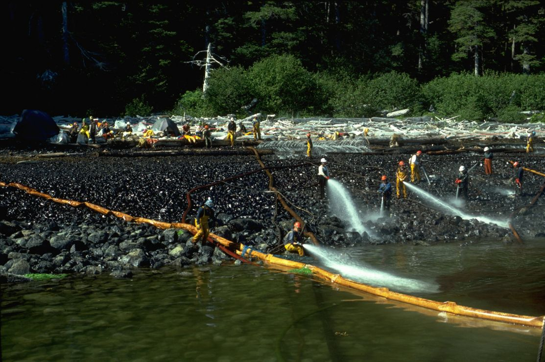 Photo of workers spraying water on rocky shore.