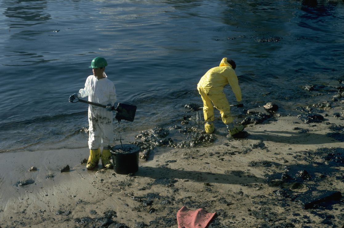 Photo of two workers shoveling black oil off of a beach.