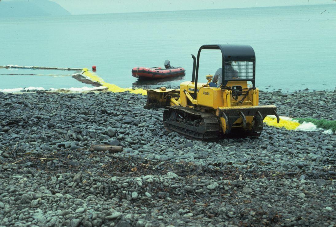 Photo of excavator on rocky shore.